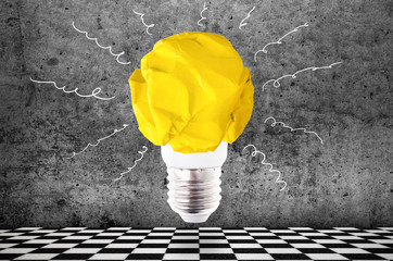 Wall Mural - crumpled yellow paper light bulb on concrete wall background