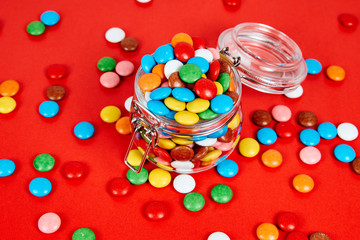 Colorful candies in glass jar isolated on red oranges background