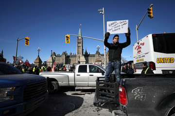 A member of the United We Roll protest convoy holds a sign in Ottawa