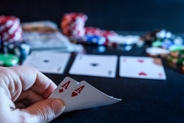 Two  aces in hand and gambling chips at black