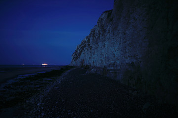 The cliff is seen with a cross channel ferry in the background making its way to Dover during sunset in Escalles, near Calais