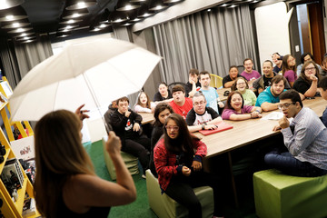"""Photography teacher Sandra Reis holds an Umbrella White Translucent as she gives lessons to her students with Down syndrome at the Galera do Click or """"Click Crowd"""" photography school in Sao Paulo"""