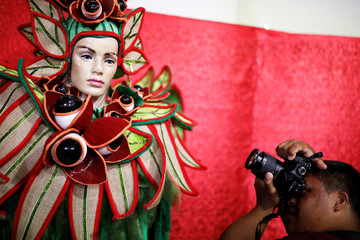 "Student with Down syndrome Joao Marcelo takes a picture of a costume at Mocidade Alegre samba school during a practice session of the Galera do Click or ""Click Crowd"" photography school in Sao Paulo"