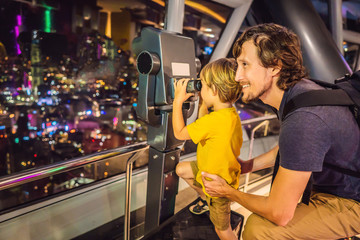 Dad and son are looking at Kuala lumpur cityscape. Use binoculars. Panoramic view of Kuala Lumpur city skyline evening at sunset skyscrapers building in Malaysia. Traveling with kids concept