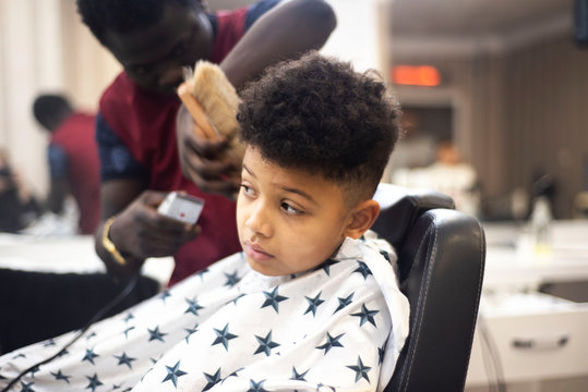 Boy in the african barbershop. Cute mixed boy makes a haircut in the African salon. Hair style. Haircut by machine for children. School boy hair style.