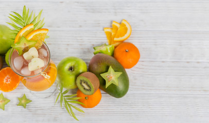 Summer cocktail with various tropical fruits around. Apple, kiwi, tangerine, orange, mango, carambola.