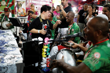 "Student with Down syndrome Bruno Pato talks with his photography teacher Sandra Reis as he takes a picture of members of Mocidade Alegre samba school during a practice session of the Galera do Click, or ""Click Crowd"" photography school in Sao Paulo"