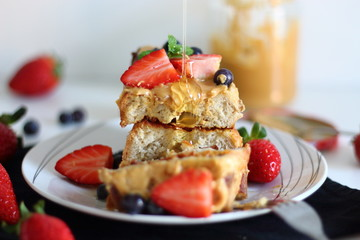 Pouring syrup over french toasts with peanut butter, strawberries and blueberries for breakfast.