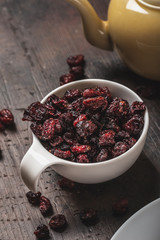 White cup full of dried red berries placed on dark wooden board