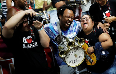 "Students with Down syndrome Felippe and Isadora laugh as they take pictures of members of Mocidade Alegre samba school during a practice session of the Galera do Click, ""Click Crowd"" photography school in Sao Paulo"