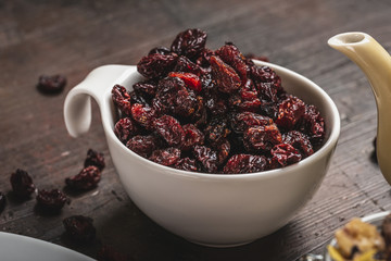 White cup full of dried red berries placed on dark board
