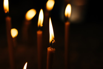 candles in black darkness environment in religious service time inside church, yellow glared bokeh effect