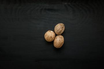 Fototapeta Close-up image of nutmeg on black wood background, view above obraz