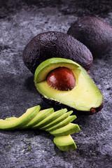 Avocado on old table. Halfs of avocado. Fruits healthy food concept