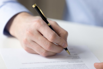 Close up male hand fill contract paper