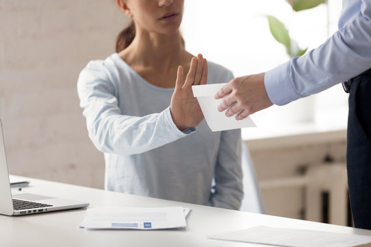 Woman refusing money in the envelope offered by man