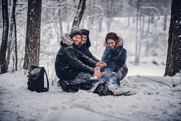 Cheerful company of students basking near a campfire in a snowy forest in winter