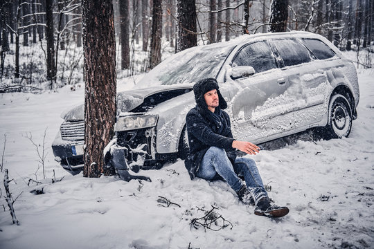 The car got into a skid and crashed into a tree on a snowy road. A frustrated driver sits on the snow and smokes a cigarette in anticipation of a tow truck