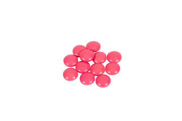 A scattering of pink pills, isolated on white background