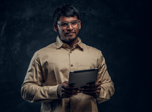 Portrait of a smart Indian male in eyewear and shirt holding a tablet computer and looking at a camera in studio against the background of the dark wall.