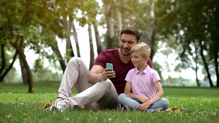 Dad and son talking with relatives via smartphone, video conference, 4g internet