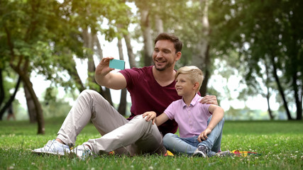 Dad and boy taking selfie on smartphone, resting in park at weekend, free time
