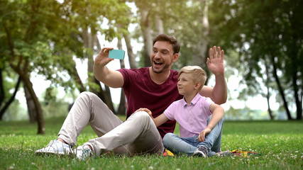 Father and son talking with mother via smartphone, video conference outdoors