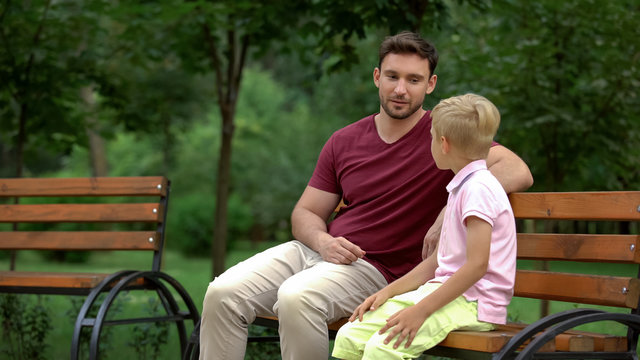 Father and son sitting on bench in park, men talks, spending time together
