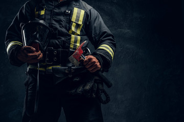 Cropped image of a male in uniform holding an oxygen mask and fire axe in the studio against a dark textured wall