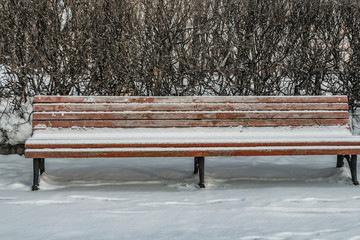 A wooden painted brown color beautiful bench with black wrought-iron legs stands with white snow in a park in winter