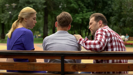 Parents talking with son on bench in park, supporting teen in time of trouble