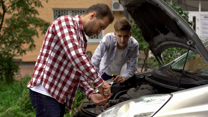 Bearded dad and his son repairing car with open hood outdoors, fixing engine