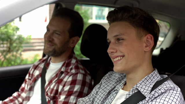 Son with father testing new bought car, dad teaching teen boy to drive auto