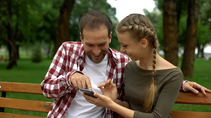 Smiling father and daughter laughing at funny photo of relative on smartphone