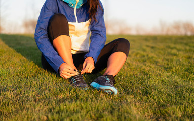 Young woman tying shoelace of sneakers to make outwork training running. Fitness and healthy lifestyle
