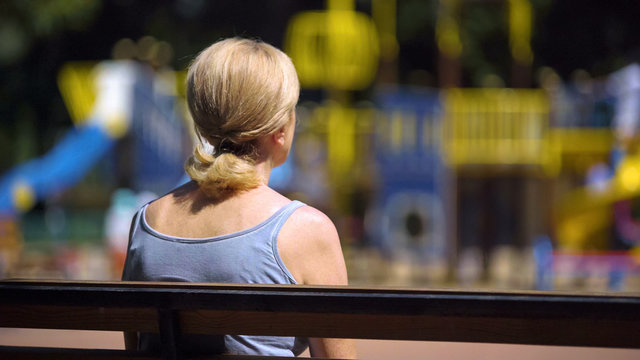 Sad old female sitting on playground bench and looking at children, infertility