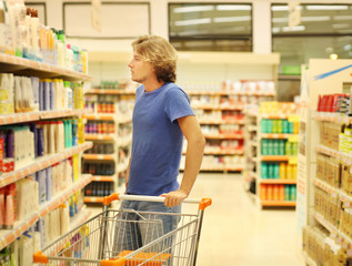 Man shopping in supermarket reading product information.(washing powder,detergent)
