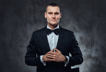 Successful elegantly dressed man wearing a black classical suit and bow tie, looking at a camera. Studio shot on a dark textured wall