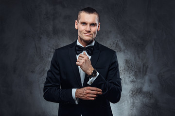 A handsome man in black suit fastening buttons on the sleeves. Studio shot on a dark textured wall