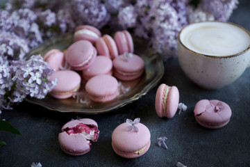 Lavander or blueberry macarons with vanilla ganache on vintage silver plate and dark stone table, decorated with lilac flowers