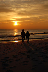 Couple in silhouette holding hands and walking along Destin beach watching a beautiful sunset