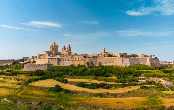 Aerial Landscape view of Mdina city - old capital of Malta country. Green fields and blue sky with clouds