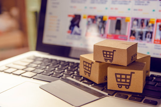Shopping online. Cardboard box with a shopping cart logo in a trolley on a laptop keyboard payment by credit card and offers home delivery.