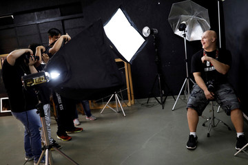 "Student with Down syndrome Felippe poses for his mates during a class at the Galera do Click or ""Click Crowd"" photography school in Sao Paulo"