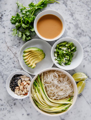 Ingredients for asian rice noodle dish with avocado, parsley, vegetables, almonds and sesame seeds