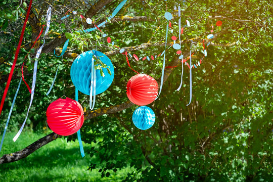 Party in garden outdoors. Preparations for the holiday and decorating the garden with balls and colored ribbons