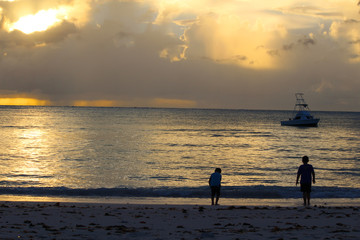 Sunset on the sea with a boat and two children on the beach, Long Island, Bahamas
