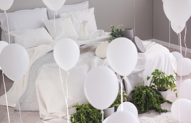 Urban jungle and bunch of white balloons in trendy bedroom with king size bed with white bedding and grey blanket