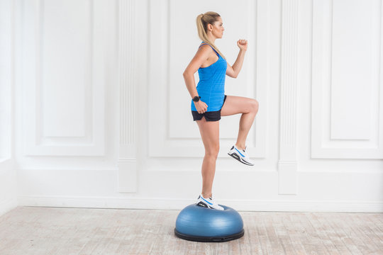 Side view portrait of concentration sporty beautiful young athletic blonde woman in black shorts and blue top working in gym doing exersice in bosu balance trainer, raised one knee on fitness ball.