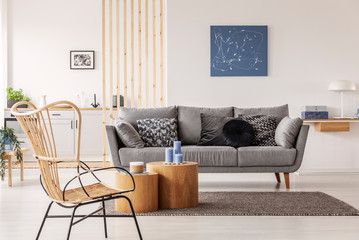 Wicker chair next to wooden block coffee table in fashionable living room interior